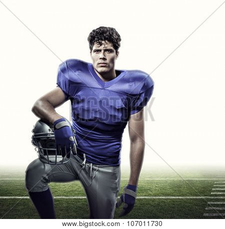 Portrait of determined American football player with hand on helmet against american football pitch