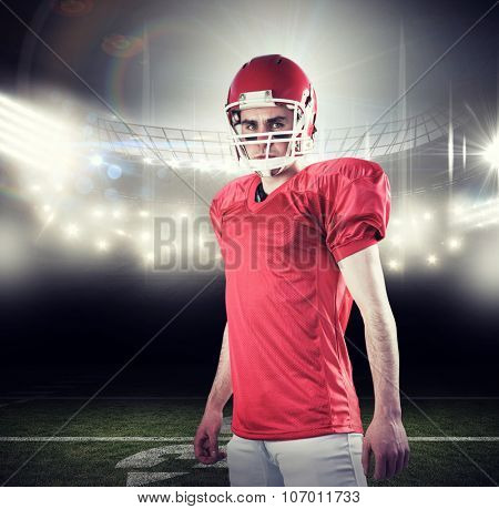A serious american football player taking his helmet looking at camera against american football arena