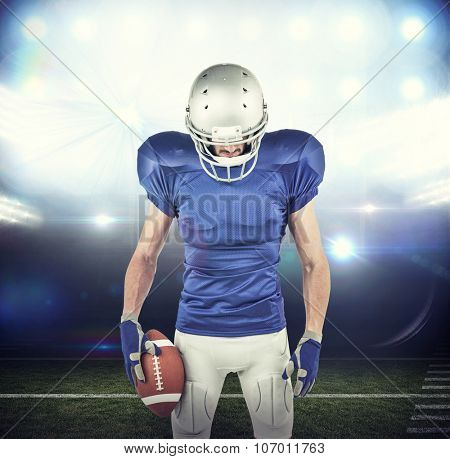 American football player looking down against american football arena