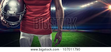 American football player holding helmet aside against rugby stadium