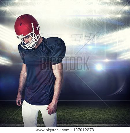Rugby player looking down against american football arena
