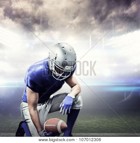 American football player kneeling while holding ball against american football arena