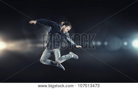 Modern style male dancer jumping in lights of spotlight
