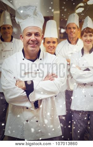 Snow against five chefs wearing uniforms while posing in a kitchen