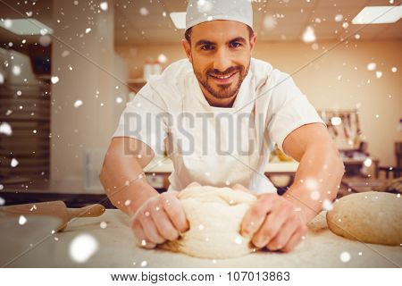 Snow against baker kneading dough at a counter