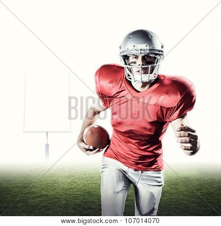 Portrait of sportsman running while playing American football against american football posts