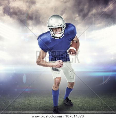 Portrait American football player holding ball against american football arena