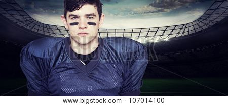 American football player looking at the camera against rugby stadium