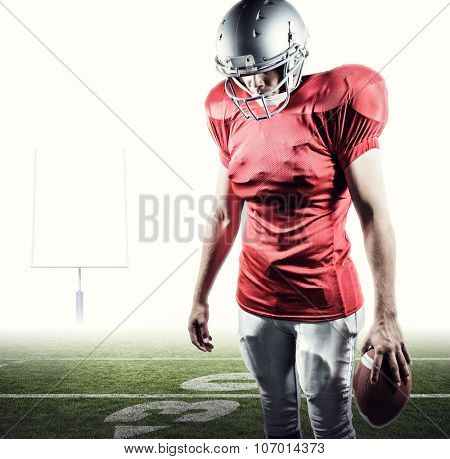 American football player looking down while standing against american football posts