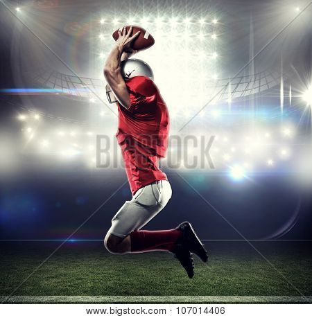 American football player in red jersey jumping against american football arena