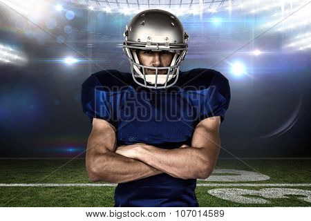 Portrait confident of American football player with arms crossed against american football arena