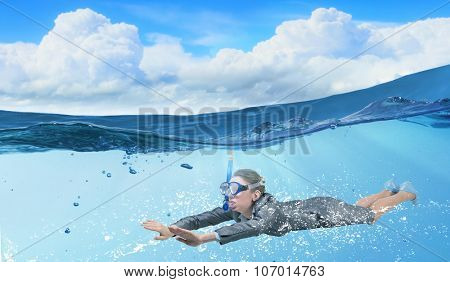 Young businesswoman in suit and diving mask swimming under water