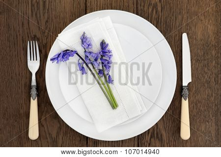 Dinner table place setting with white porcelain dishes, bluebell flowers, antique cutlery and  linen napkin over old oak background.