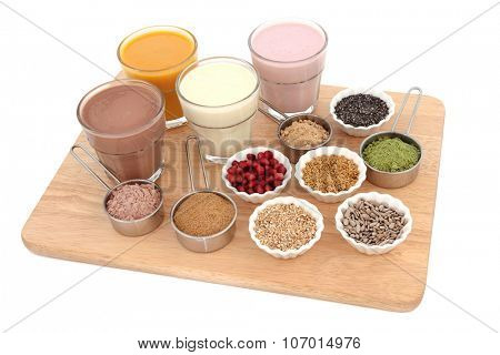 Body building health food with protein and fruit juice shakes, chocolate whey, wheatgrass, pomegranate and maca powder, seeds and oatmeal on a beech wood board over white background.