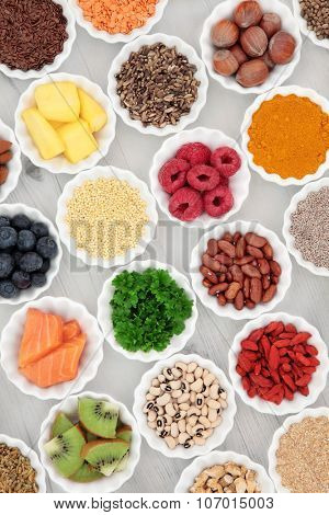 Healthy super food selection in porcelain crinkle bowls over distressed wooden background. High in vitamins and antioxidants.