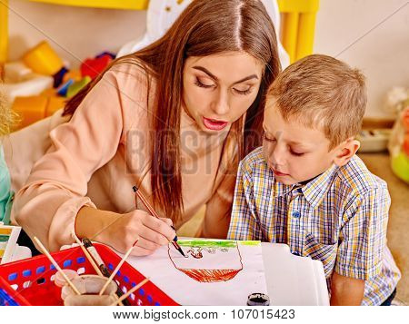 Woman with kids holding colored paper and glue on table in kindergarten .