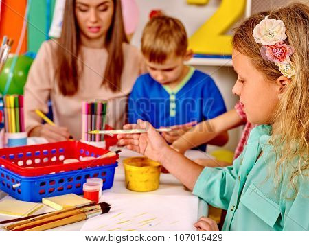Group kids with teacher holding colored paper and glue on table in kindergarten .