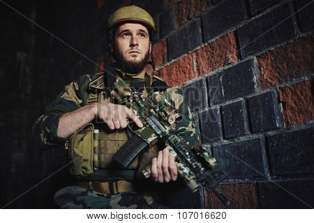Young soldier of special forces standing against brick wall with gun