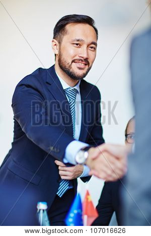 Asian businessman handshaking with his partner after negotiation