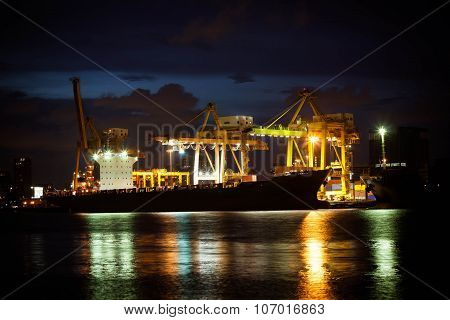 Cranes Unloading A Ship In A Harbor