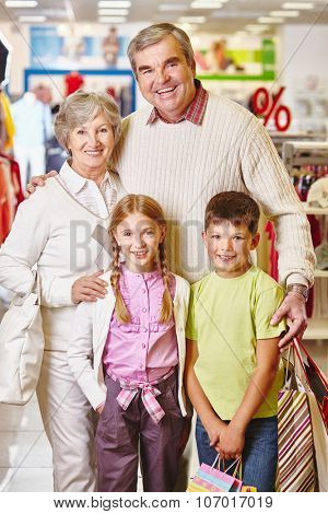 Happy grandparents and their grandchildren with paperbags visiting sale in the mall before Christmas