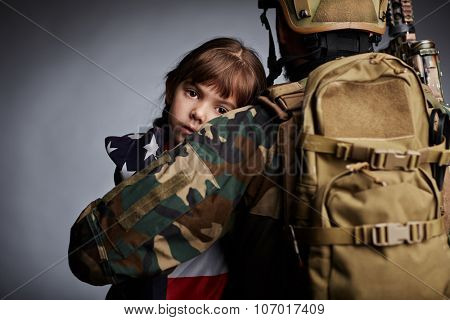 Affectionate girl looking at camera out of her father back in camouflage