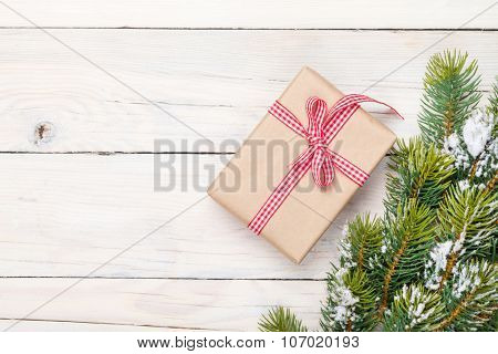 Christmas fir tree with snow and gift box on rustic wooden board with copy space