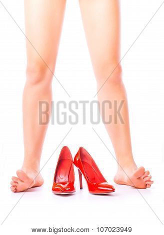 Women bare legs and red shoes on a white background