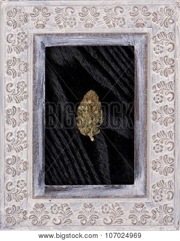 Marijuana bud on black wood background and wooden frame