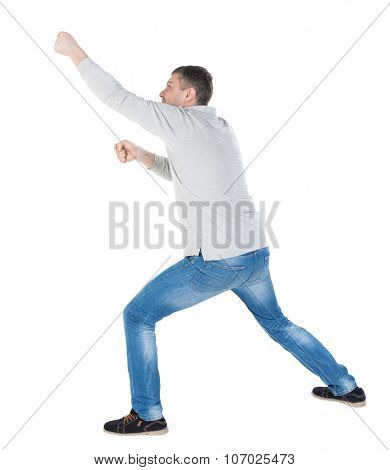 back view of standing man pulling a rope from the top or cling to something. guy watching. Rear view people collection.  backside view of person.  Isolated over white background.