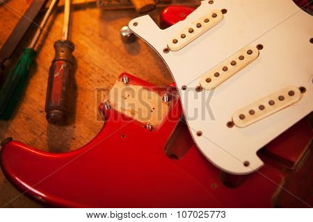 Red electric guitar on guitar repair desk or in a repair work bench. Neck and pickguard detached. Solid body guitar, red metallic color. Shallow depth of field.