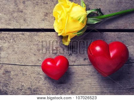 Red  Decorative Hearts  And Rose Flower On Aged Wooden Background.