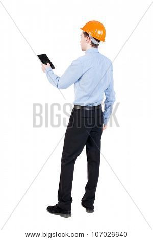 Backview business man in construction helmet stands and enjoys tablet or using a mobile phone. Standing young guy. Rear view people collection. backside view of person. Isolated over white background.