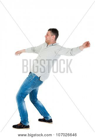 Back view man Balances waving his arms. Rear view people collection. backside view of person.  Isolated over white background. A guy in a gray jacket at the time of the fall.