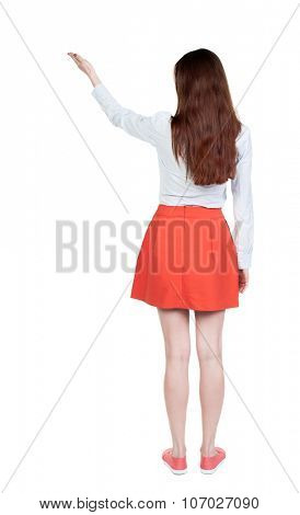 Back view of  pointing woman. beautiful girl. Rear view people collection.  backside view of person.  Isolated over white background. A girl in a short skirt palm of the hand shows up.