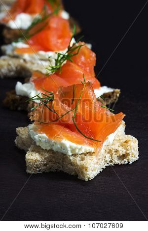Canapes In Star Shape With Smoked Salmon On Dark Brown Wood, For Christmas Or New Year
