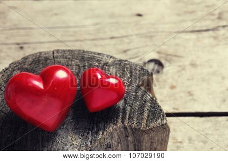 Red  Decorative Hearts On Aged Wooden Background.