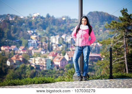 Young woman posing outdoor in autumn. Fashion portrait of pretty girl in cold weather wearing a pink