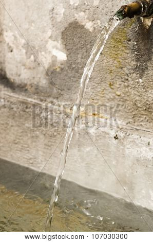 Detail of a public fountain where sgroga a gush of water