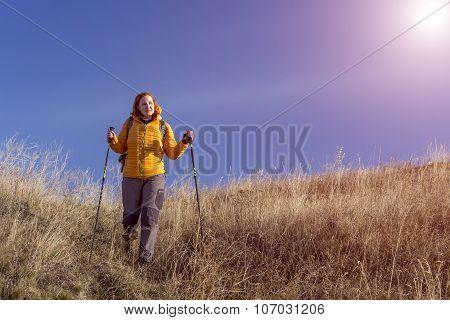 Happy female hiker walking down on grassy hill