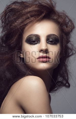 Fashion studio portrait of young beautiful woman with shaggy hairstyle and smoky eyes make-up