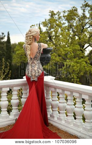 Beautiful Sexy Woman With Elegant Hair Style In Mermaid Red Dress On The Balcony Enjoying Park View.
