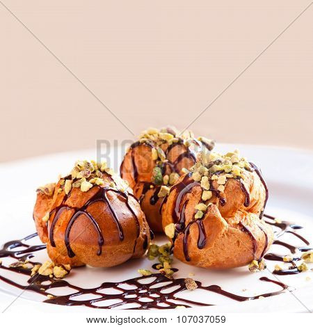 profiteroles with chocolate sauce on white plate close-up