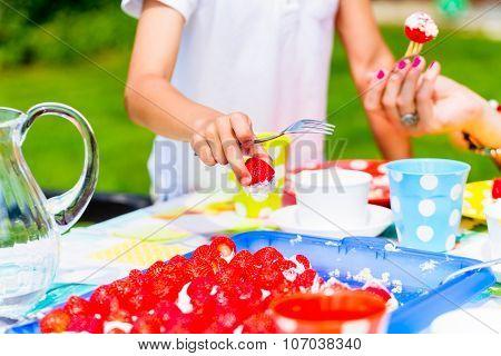 Girls cutting piece of strawberry cake in garden