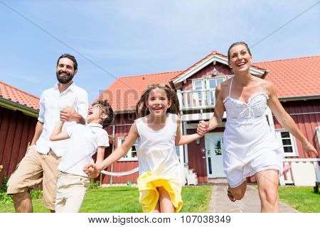 Happy family running on meadow in front of house on front yard grass