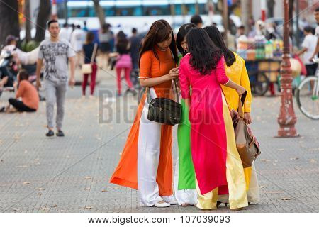 HO CHI MINH, VIETNAM, FEBRUARY 25, 2015 : Vietnamese girls in traditional Ao Dai dresses taking photos near the post office in Ho Chi Minh city (Saigon), Vietnam