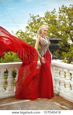 Fashion Beauty Outdoor Portrait Of Beautiful Woman In Red Dress Posing On The Balcony With Balustrad
