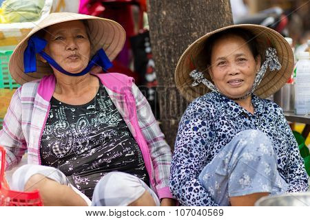 HO CHI MINH VILLE, VIETNAM, FEBRUARY 26, 2015 : Two friendly vegetable sellers are posing in the street of Chinatown in Ho Chi Minh Ville, (Saigon), Vietnam.