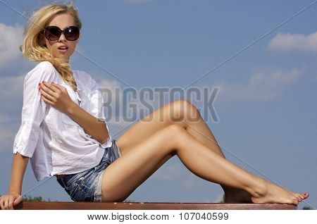 Portrait of beautiful young adult attractive sexy and sensuality pretty blonde girl in sunglasses and white shirt on background blue sky