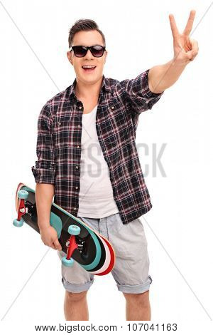 Vertical shot of a young male skater holding a skateboard and making a peace hand gesture isolated on white background